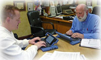 Image of two men at work using a Ubi-Duo communication device.