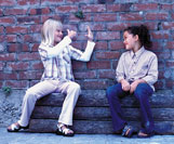 Two young girls using sign language outside