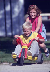 Boy on a tricycle and girl playing.